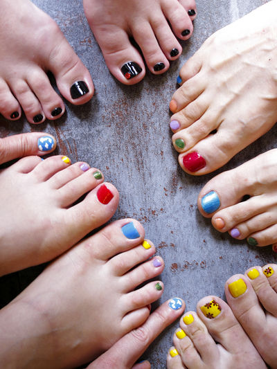 Four woman relaxing and coloring nails, multi colored nails, 8 feet, 2 fingers People Feet Real People Women Beautiful Woman Finger Nail Polish Friendship Nail Group Adult Close-up Variation Lifestyles Body Part Fingernail High Angle View Group Of People Multi Colored Human Foot Leisure Activity Human Body Part Human Finger