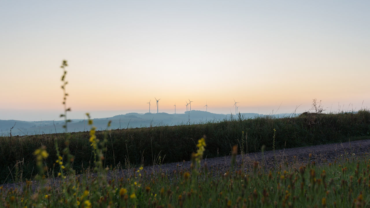 sky, beauty in nature, sunset, plant, environment, scenics - nature, tranquility, tranquil scene, field, landscape, land, growth, nature, clear sky, non-urban scene, no people, mountain, fuel and power generation, outdoors, orange color
