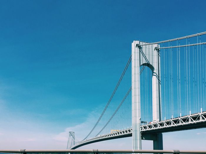 Low angle view of verrazano–narrows bridge against blue sky