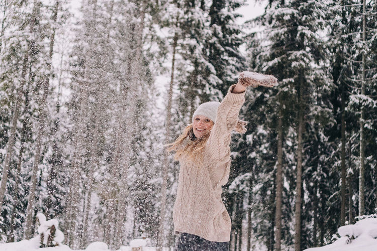 Woman standing on snow covered trees in forest