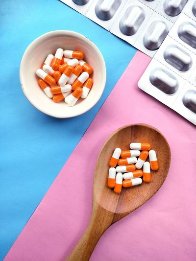 High angle view of wooden spoon with pills