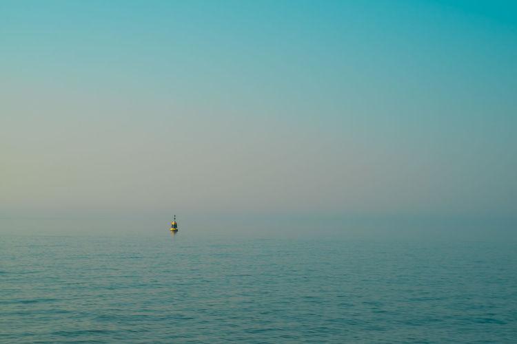 Sea against foggy sky