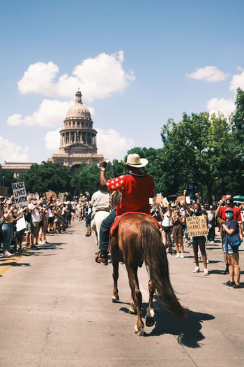 People riding horses on town square against sky