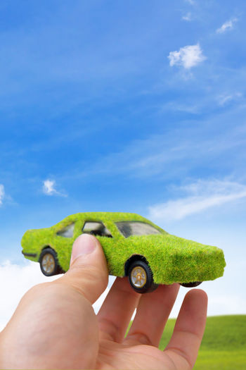 Hand Holding Eco car icon concept Eco Economics Ecosystem  Green Color Car Cloud - Sky Ecofriendly Ecological Ecology Green Color Holding Human Body Part Human Finger Human Hand Power And Energy Sky