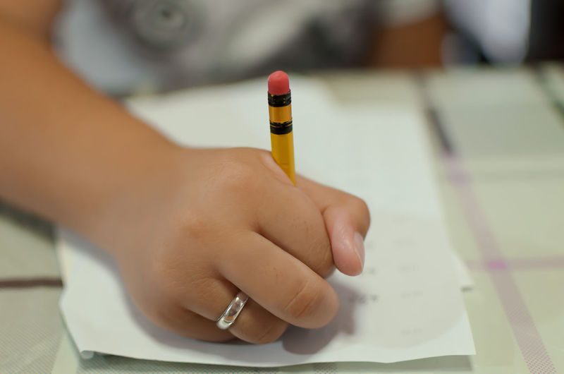 Young boy doing his school assignment Homework Assignment School Education Learning Human Hand Education Business Finance And Industry Close-up Eraser Finger Human Finger Pencil Drawing Index Finger Thumb Pencil Body Part School Supplies