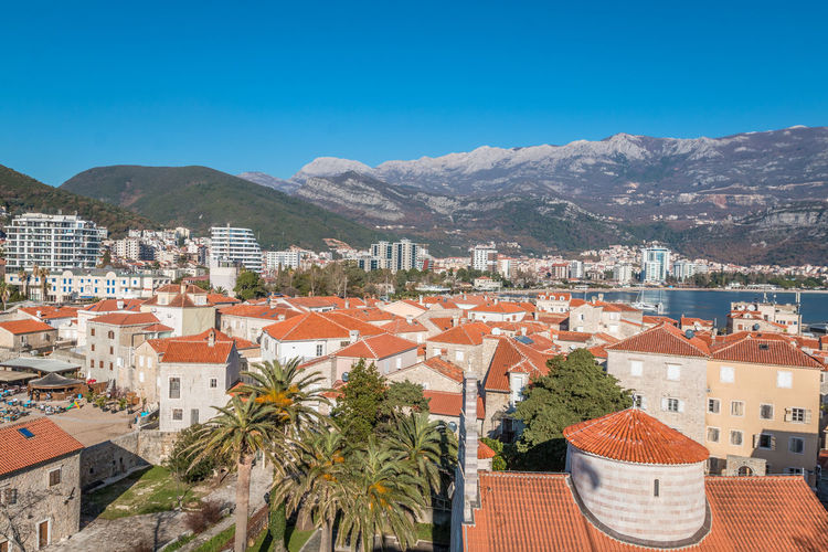 Budva city in Montenegro Budva Montenegro Architecture Building Exterior Built Structure Mountain Building Tree Sky City Residential District Plant Nature Clear Sky Blue Day High Angle View Roof Mountain Range Palm Tree No People Outdoors Cityscape TOWNSCAPE