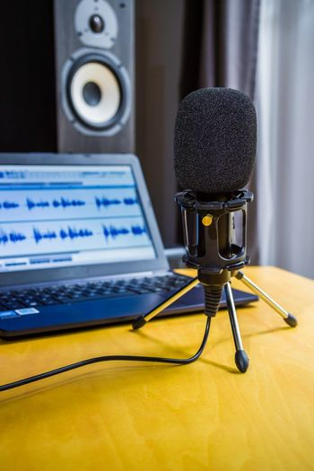Close-up of microphone by laptop on table