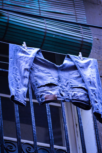 Low angle view of clothes drying against blue window