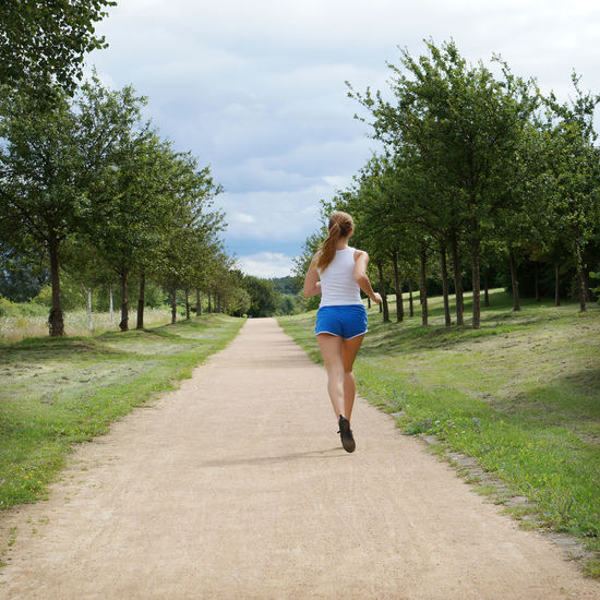 Rear view of woman jogging on footpath amidst field