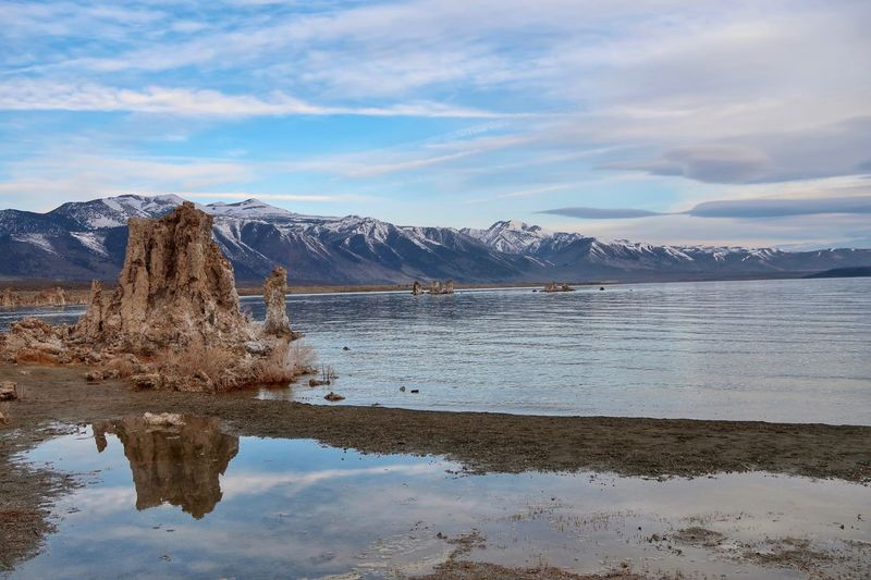 Landscape of Mono Lake and a large tufa formation with mountains in the background Mono Lake Tufa Water Sky Cloud - Sky Reflection Nature Beauty In Nature Tranquility Mountain Tranquil Scene Day No People Lake Snow Winter Cold Temperature Mountain Range Non-urban Scene Outdoors Snowcapped Mountain Scenics - Nature