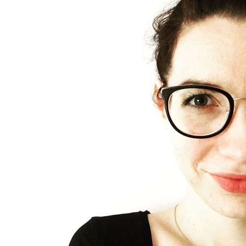 Close-up portrait of young woman in eyeglasses against white background