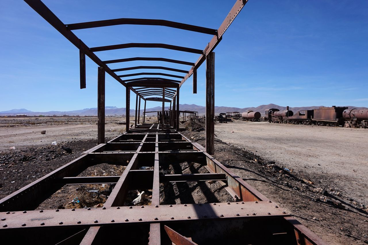 rail transportation, transportation, day, metal, sky, no people, track, railroad track, nature, architecture, diminishing perspective, built structure, abandoned, the way forward, rusty, sunlight, direction, outdoors, mountain, mode of transportation