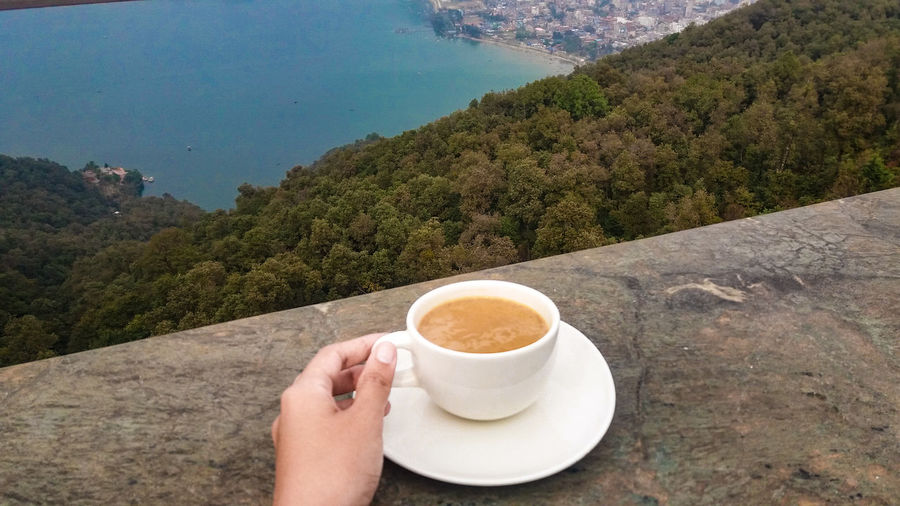 Cropped hand holding coffee cup against sea