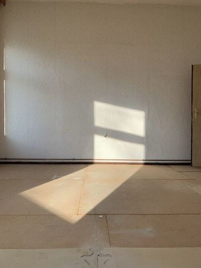 Sunlight on floor against wall at home