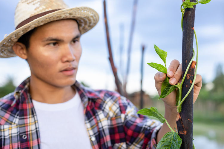 Portrait of young man holding plant