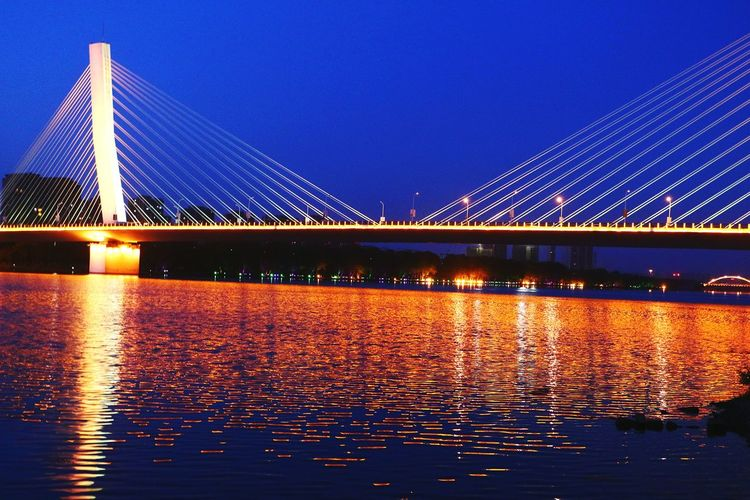 Bridge - Man Made Structure Suspension Bridge Night Connection Long Exposure Illuminated Sky River Architecture Light Trail Outdoors Business Finance And Industry Transportation Travel Water Travel Destinations Built Structure Clear Sky City Cityscape