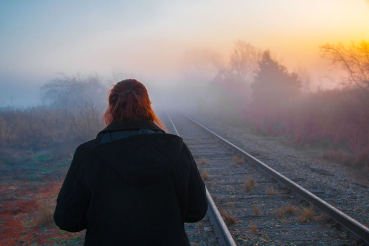 Rear view of person standing by railroad track during sunset
