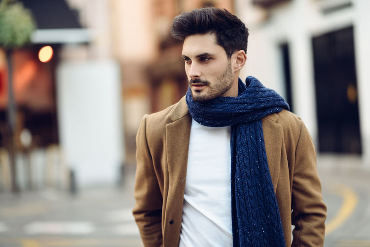 Young man wearing winter clothes in the street. Young bearded guy with modern hairstyle with coat, scarf, blue jeans and t-shirt. Winter Clothes Architecture Beard Beautiful People Cardigan Sweater City Clothing Facial Hair Focus On Foreground Front View Handsome Lifestyles Looking Men One Person Outdoors Portrait Scarf Standing Street Warm Clothing Young Adult Young Men