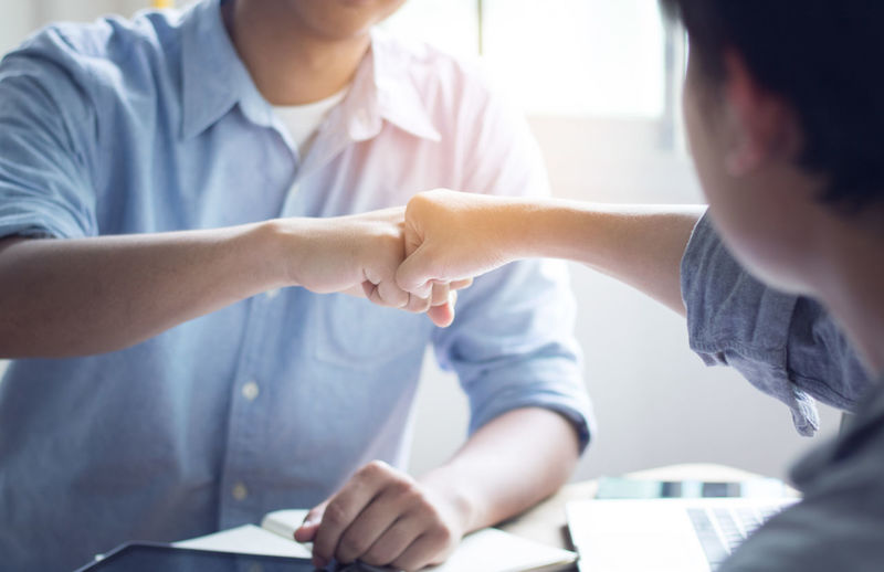 Close-up of business colleagues bumping fist in office