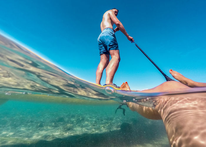 Low angle view of friends enjoying at sea against clear blue sky