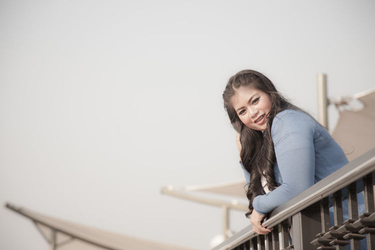 Young Woman Leaning On Railing Against Clear Sky