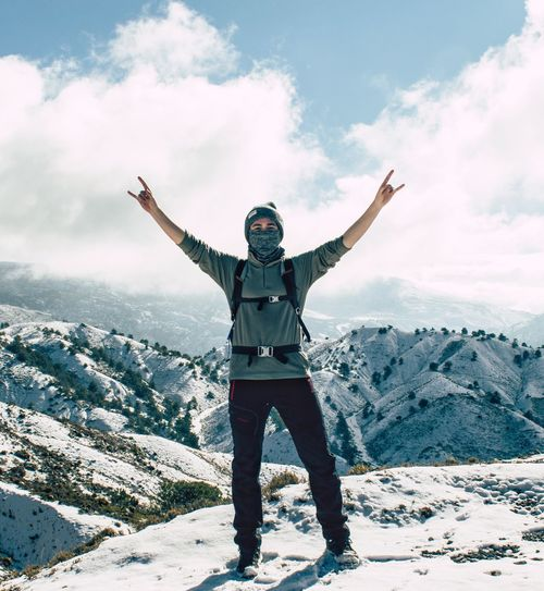 Man with arms outstretched standing on snow covered mountains against sky