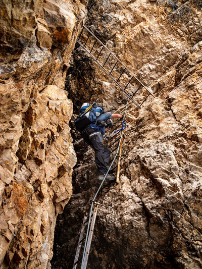 Dolomites, Italy Activity Adventure Challenge Climbing Climbing Equipment Determination Effort Extreme Sports Full Length Helmet One Person Outdoors RISK Rock Rock - Object Rock Climbing Rock Formation Rope Safety Safety Harness Skill  Solid Sport Strength