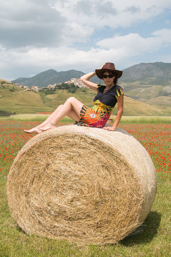 Portrait of woman wearing hat while sitting on hay bale