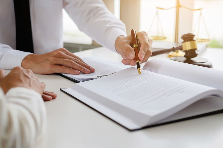 Midsection of judge writing on table while colleague sitting