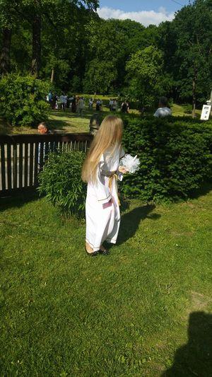 Girl Wearing White Dress Standing On Grassy Field