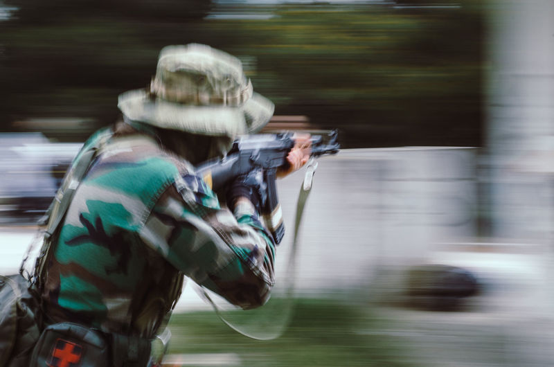 Blurred motion soldier Men One Person Blurred Motion Real People Motion Clothing Sport Holding Day Aiming Gun Weapon Activity Occupation Three Quarter Length Waist Up Outdoors Security Headwear Uniform Government Airsoft