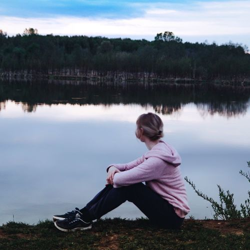 Side view of young woman sitting by lake against sky