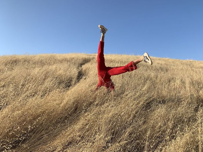 Man doing handstand on field against clear sky