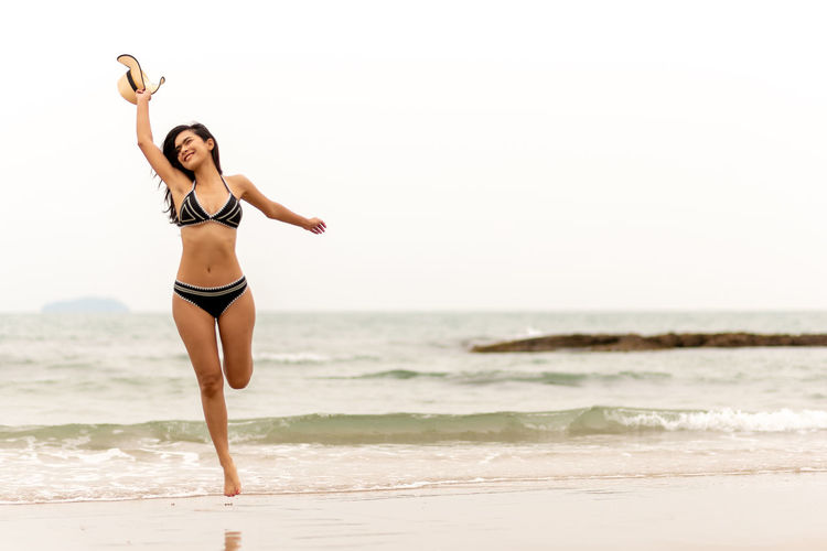 Sea Water Beach Clothing Full Length Land Leisure Activity One Person Lifestyles Sky Young Women Horizon Over Water Bikini Young Adult Beautiful Woman Swimwear Standing Beauty Sport Arms Raised Human Arm Limb Hairstyle