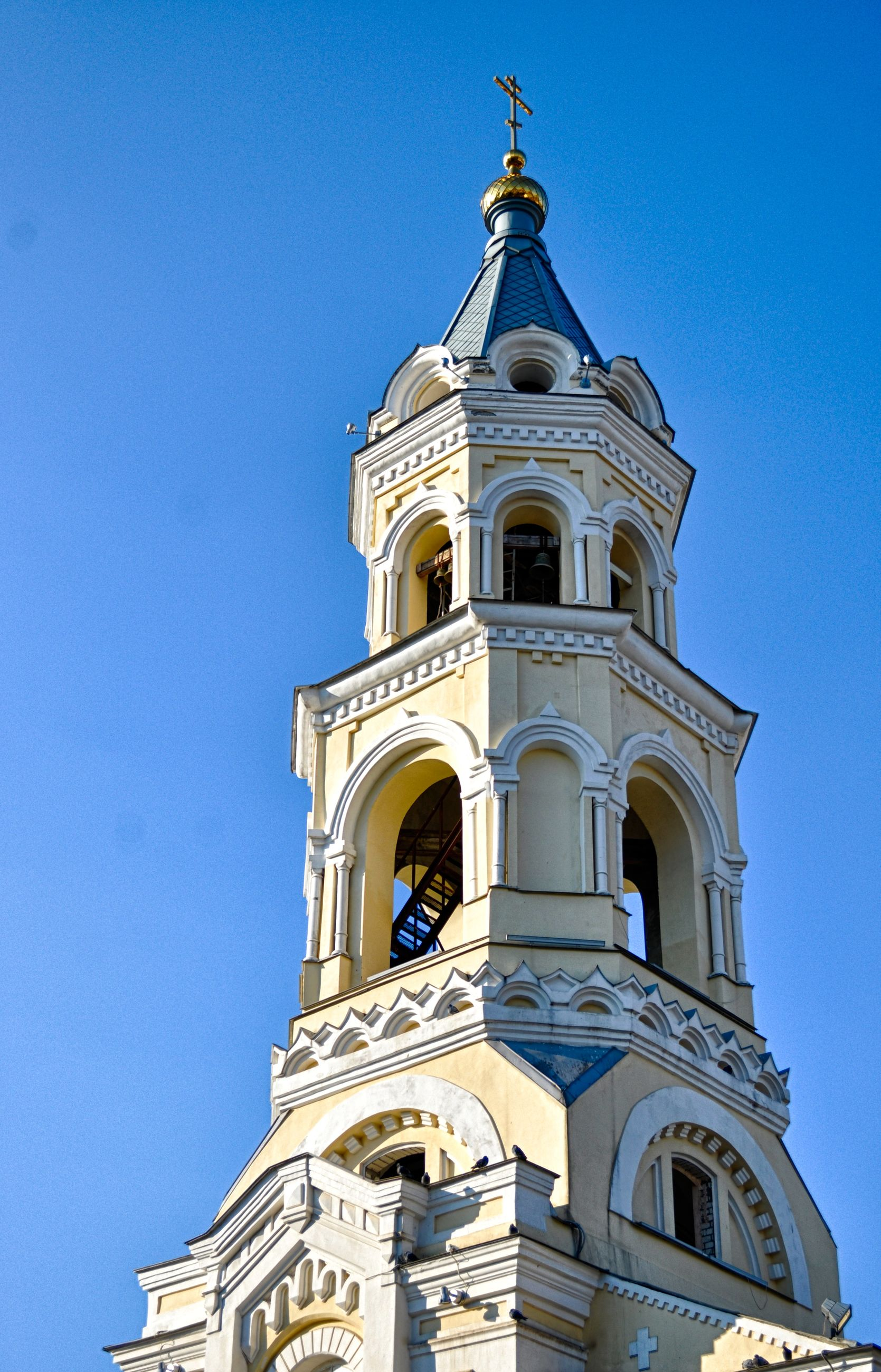 religion, architecture, building exterior, place of worship, church, low angle view, built structure, spirituality, clear sky, blue, cathedral, clock tower, high section, tower, cross, clock, day, bell tower