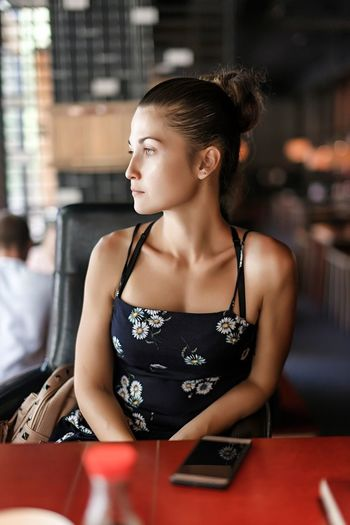 Young woman looking away while sitting in restaurant