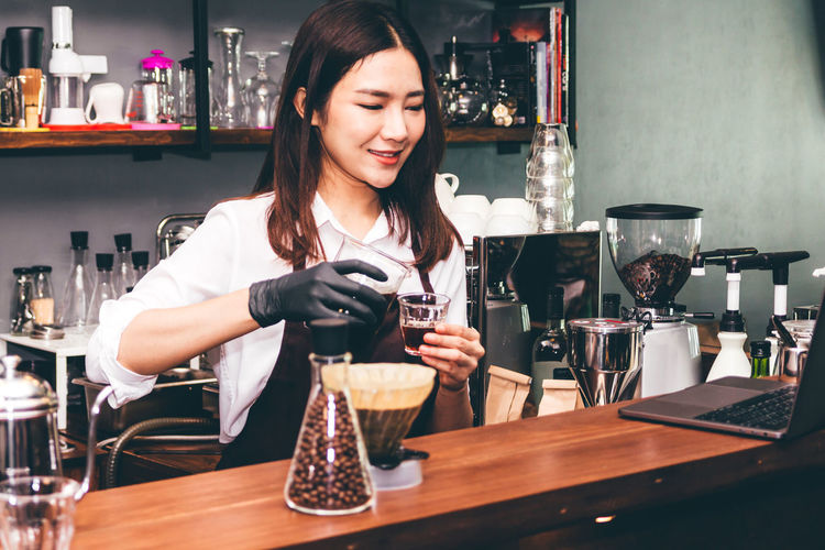 Barista holding milk for make coffee latte art in coffee shop Adult Alcohol Bar Counter Bartender Business Drink Food And Drink Glass Hairstyle Holding Indoors  Lifestyles Occupation One Person Pouring Preparation  Real People Refreshment Table Waist Up Women Working Young Adult Young Women
