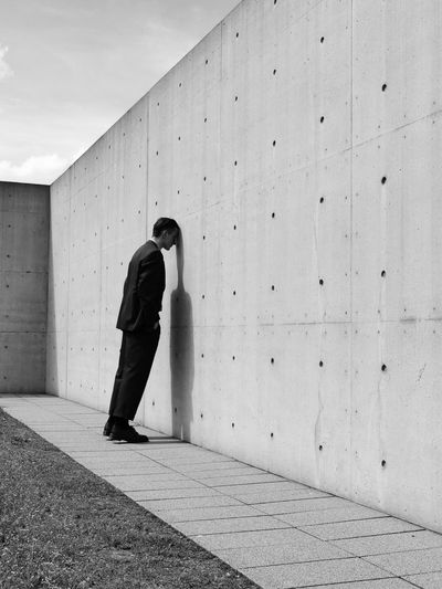 Full length of depressed man standing by wall