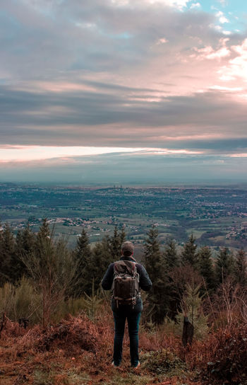Rear View Of Man With Backpack Standing On Mountain Against Cloudy Sky During Sunset
