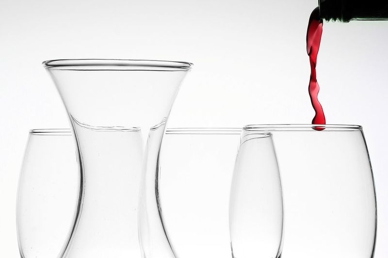 Close-up of wineglass on glass against white background
