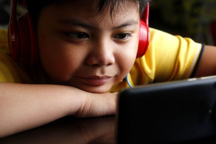 Close-up of boy using phone while listening music at home