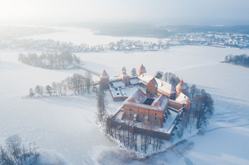 Winter castle in lake island, Trakai, Lithuania Aerial View Ancient Aerial Architecture Castle Cold Temperature Europe Famous Place Fort Fortification Fortress Historic Ice Snow Island Lake Landmark Lietuva Lithuania Trakai Mansion Medieval Old Season  Tower Tourism Tourist Attraction  Winter White Building Built Structure Landscape Snowing Water