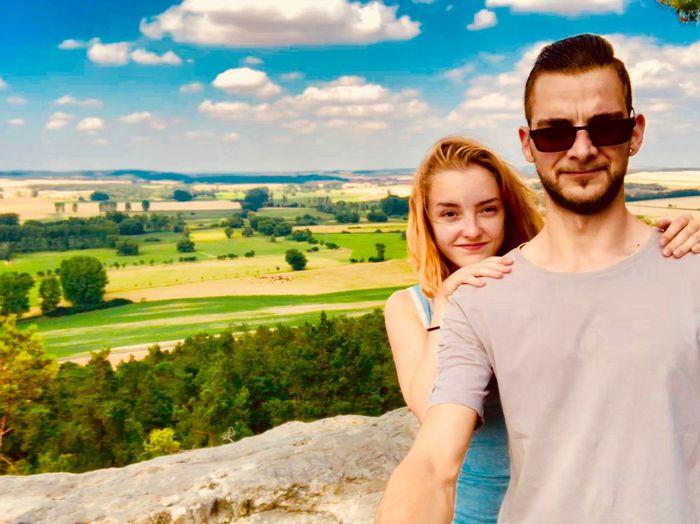 Portrait of young couple wearing sunglasses against landscape
