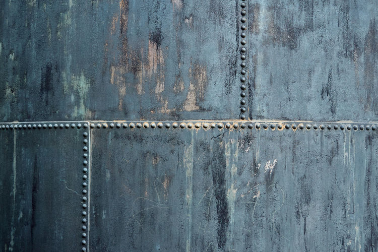 Part of an old storage container made of riveted iron plates, used and dirty, pattern, texture