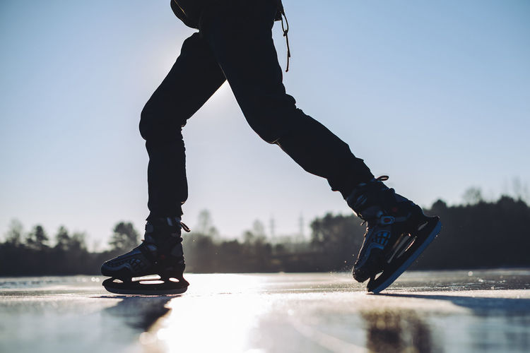 Low section of man ice-skating against clear sky