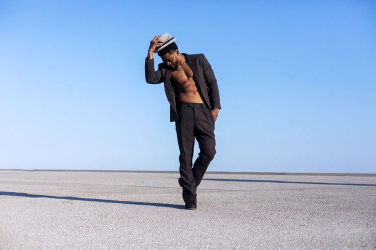 Front view of a black bearded man holding a hat while dancing and enjoying against blue sky in a sunny day One Person Full Length Adult Day Men Sky Business Person Business Nature Well-dressed Businessman Suit Standing Environment Corporate Business Outdoors Side View Clear Sky Young Adult Effort African American Black Man Dancing Muscular Build Suit Daylight Blue Sky Copy Space Males  Man Bearded Elegant Attractive Wellbeing