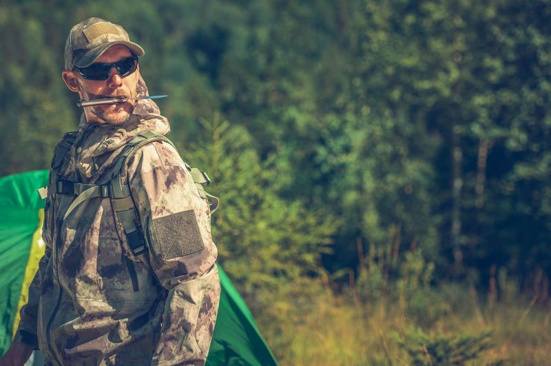Army Solider Wearing Sunglasses While Standing Against Trees In Forest