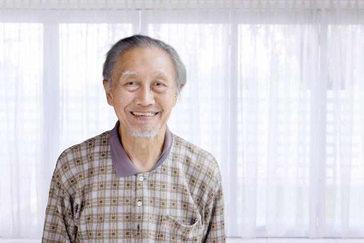 Portrait of smiling senior man against window at home
