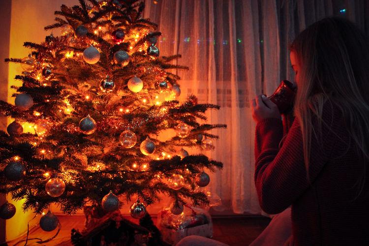 Woman Drinking Coffee By Illuminated Christmas Tree