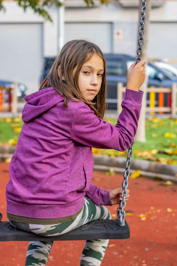 Portrait of girl sitting on swing at playground